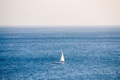 Lonely sailboat in the open sea royalty free stock photography