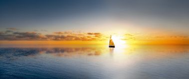 Lone sailboat at sunset. Boat On Ocean at sunset Stock Photos