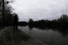 A lone shadow blurred, ghostly hooded figure looking out on a river on a winters day. With a cold, grunge edit.  royalty free stock images