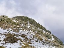 Lone sheep on snowy rocky area. Snowy rocky area on Rosthwaite Fell with lone sheep Stock Photos