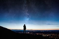 A lone silhouetted hooded figure. Standing on a hill looking down on city lights at night with a galaxy and stars rising in the ni. Ght sky stock photo