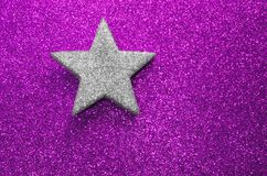 Lone silver star silver on glitter material on purple background. Lone silver star on purple shiny background blazing bright Stock Photo