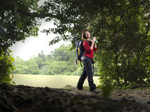 Lone single female trekking through the forest stock photo