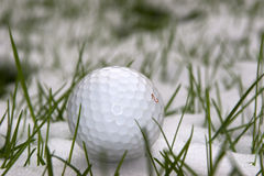 A lone single golf ball in the snow