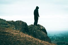 A lone sinister, hooded figure standing on a rocky outcrop looking out from top of a hill. With muted edit royalty free stock photography
