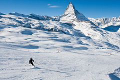 Lone Skier on Mountain. A lone skier goes down the snow covered mountain in the Swiss Alps with the Matterhorn peak in the background stock photos