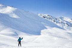 Lone skier waving on a snowy mountain peak. Covered in pristine fresh white powder as he or she prepares to descend the ski run in a beautiful cold sunny winter stock photos