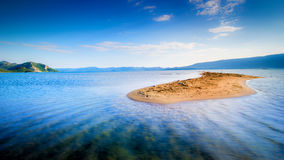Lone small sandy island in the middle of blue sea Stock Photography