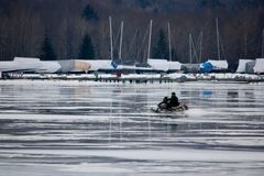 Lone snowmobile on a frozen lake. A snowmobile crossing a shiny frozen lake towards the shore covered with shrink wrapped boats stored for the winter Stock Photography