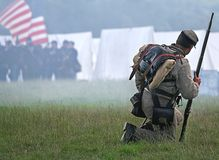 Lone Soldier. Civil War action as lone Soldier drops to knees to meet his fate as smoke from Muskets rises stock image
