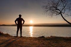 Lone sportsman looking at colorful  sunset on shore of autumn lake Royalty Free Stock Image