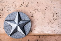 Lone Star of Texas Silver emblem on pink concrete. Closeup image metallic lone star inside circle. Emblem of Texas. Mounted on pink concrete background. Copy stock photography
