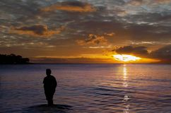 Lone on sunset . The silhouette of lone walking person is on the sunset beach. The tropical sea, sunset cloudscape as  background Stock Photo