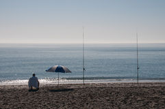 Lone surf fisherman and parasol at beach Royalty Free Stock Image