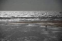 Lone Surfer on a Beach. Lone surfer in silhouette walking on a beach with a bodyboard stock images