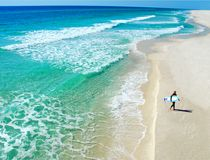 Lone Surfer on Beach. Lone surfer walking on deserted beach next to beautiful ocean Stock Photos