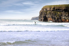 Lone surfer near cliffs Royalty Free Stock Photography
