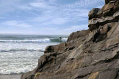 Lone surfer near rocks Royalty Free Stock Image