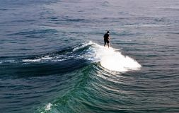 A lone surfer on riding a wave on a surf board on the Pacific ocean. In southern California, USA in summertime Royalty Free Stock Photos