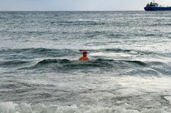 Lone swimmer in a Santa Claus hat royalty free stock photo