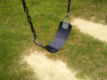 Lone Swing. Single black swing on the playground Stock Photos