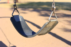 A Lone Swing. A solitary swing in a deserted playground Royalty Free Stock Photography