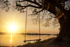 Lone swing at river side and sunset ,Thailand Stock Photo
