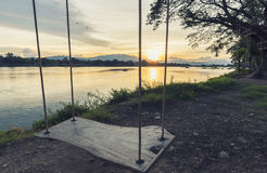 Lone swing at river side and sunset ,Thailand . Vintage Tone. Royalty Free Stock Photo