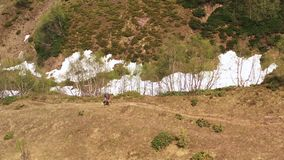 Lone tourist with panama trekking poles and baby in hiking carrying. Trekking route in mountain aerial landscape. Lone tourist with panama trekking poles  and stock video footage