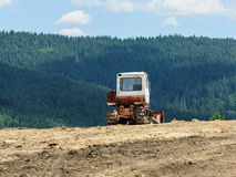 Lone tractor in mountain forest in background. Green pines Royalty Free Stock Photos