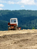 Lone tractor in mountain forest in background. Scene Royalty Free Stock Image