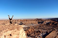 Lone traveler doing a handstand on the edge of the cliff at Valle de la Luna chile Royalty Free Stock Image