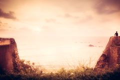 Lone traveler man on cliff looking with inspiration at horizon with sunlight during sunset with effect of light at the end of tunn stock image