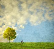 Lone tree with human figure running. Environmental background Stock Photography
