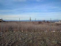 Lone tree panorama. Panoramic horizon view of wire fence limiting vast field with a single tree Royalty Free Stock Photos