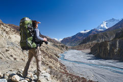 Lone trekker with a backpack. In the mountains of Nepal, looking into the distance royalty free stock image