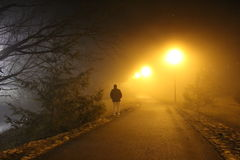 Lone walker on a misty fog covered path tennessee. Orange lights Foggy path person walking Stock Image