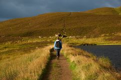 A lone walker on a mountain path. A lone hill walker hiking along a path in Scottish highlands Royalty Free Stock Image