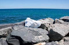 Lone White Rock on the Breakwater Stock Images