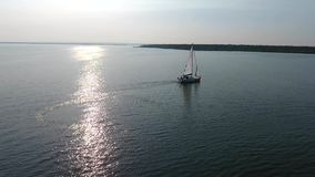A lone white sailboat. Floats on the sea, against the backdrop of the sunset. The glare of the sun is displayed on the water surface stock video footage