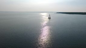 A lone white sailboat. Floats on the sea, against the backdrop of the sunset. The glare of the sun is displayed on the water surface stock footage