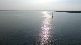 A lone white sailboat. Floats on the sea, against the backdrop of the sunset. The glare of the sun is displayed on the water surface stock video