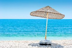 Lone wicker umbrella on beach Stock Images