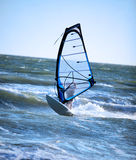 Lone windsurfer. Lone anonymous winsurfer in the ocean catching a wave stock photo