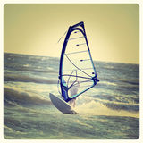 Lone windsurfer. Lone anonymous winsurfer in the ocean catching a wave with Instagram effect filter royalty free stock image