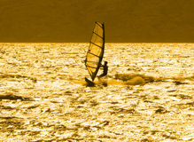 Lone windsurfer at sunset. A young windsurfer is alone in the ocean at sunset. On the south shore of Maui, Hawaii Stock Images