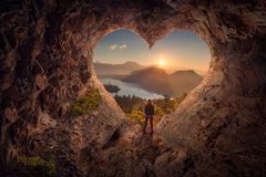 Young woman in heart shape cave towards the idyllic unrise