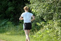 Lone woman jogging. Female jogging through woods Royalty Free Stock Photos