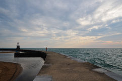 Lone woman at Lake Michigan. A woman stands alone as the sun rises over Lake Michigan Stock Photo