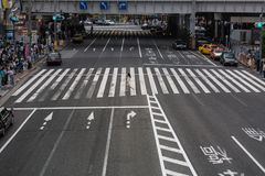 A lone woman runs across a busy intersection in Tokyo, Japan. A busy street scene in Tokyo, Japan Royalty Free Stock Photos